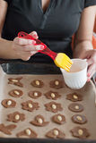 Glazing christmas cookies before backing with egg Royalty Free Stock Photo