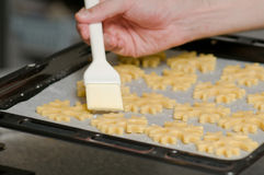 Glazing cookies on backing paper in a tray Stock Image