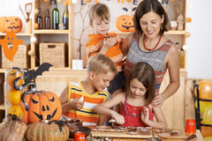 Glazing cookies. Mother and children glazing cookies for Halloween celebration Stock Photo