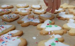 Glazing cookies. Pouring over glazing mass over dough pieces Stock Photos