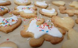 Glazing cookies. Pouring over glazing mass over dough pieces Stock Photography