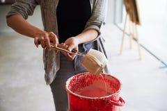 Glazing mug. Cropped image of female artist glazing ceramic mug she made Royalty Free Stock Photos