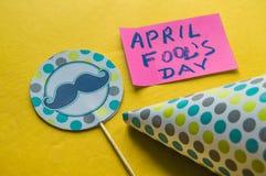 GLB, topper met een snor en de nota's met de uitdrukking April voor de gek houden de dag van ` s op een gele achtergrond Royalty-vrije Stock Foto