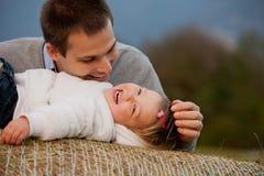 Glück ist ein Vater, der von seiner kleinen Tochter bezaubert wird Stockfotografie