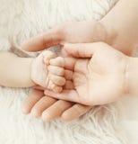 Glückeltern! Nahaufnahmehandbaby in den Händen Mutter und Vater Lizenzfreie Stockfotos
