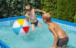 Glückkinder am Pool Stockbild