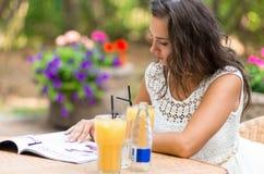 Glücklich, positiv, schön, verlegen das Eleganzmädchen, das am Café sitzt, draußen Lizenzfreie Stockfotos