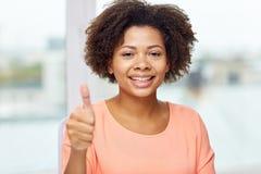 Glückliche afrikanische junge Frau, die sich Daumen zeigt Stockbilder