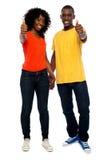 Glückliche afrikanische Paare, die sich Daumen zeigen Lizenzfreie Stockfotos