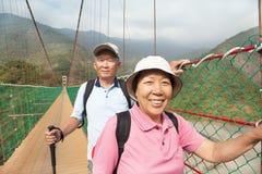 Glückliche asiatische ältere Paare, die herein auf die Brücke gehen Lizenzfreies Stockfoto