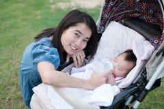 Glückliche asiatische Mutter, die dem Baby auf dem Spaziergänger einzieht Stockfoto