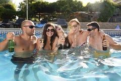 Glückliche attraktive Männer und Frauen im Bikini, der Bad an trinkendem Bier des Hotelerholungsort-Swimmingpools hat Stockbilder