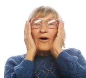 Glückliche überraschte ältere Frau, die Kamera betrachtet Stockfotos