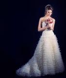 Glückliche Braut der schönen leichten Frau in einem weißen Hochzeitskleid mit einer Zugkabine mit einer schönen Hochzeitsfrisur m Lizenzfreie Stockfotos