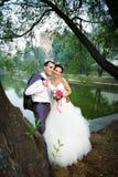 Glückliche Braut und Bräutigam auf Küste von See Stockbild
