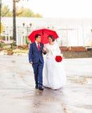 Glückliche Braut und Bräutigam an der Hochzeit gehen mit rotem Regenschirm Herbstartkonzept Lizenzfreies Stockfoto