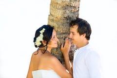 Glückliche Braut und Bräutigam, die Spaß auf einem tropischen Strand unter dem p hat Stockfotos