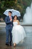 Glückliche Braut und Bräutigam am Hochzeitsweg-Weißregenschirm Lizenzfreie Stockbilder