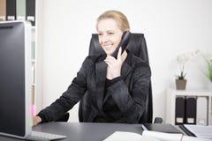 Glückliche Büro-Frau, die mit jemand am Telefon spricht Stockfoto