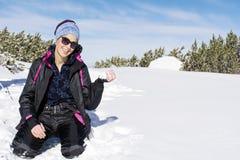 Glückliche Brunettefrau, die mit einem Schnee im Berg, den Winterschnee genießend spielt Lizenzfreie Stockfotos