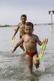 Glückliche childs spielen in Meer mit watergun, Ferien in Italien Lizenzfreies Stockfoto