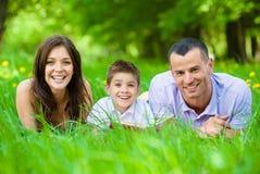 Glückliche dreiköpfige Familie, die auf Gras mit Buch liegt Stockfotos