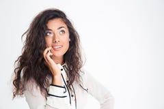Glückliche durchdachte Geschäftsfrau, die am Telefon spricht Stockfotos