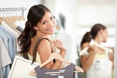 Glückliche Einkaufsfrau im Bekleidungsgeschäft Stockfotos