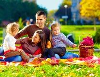 Glückliche Familie auf Herbstpicknick im Park Stockfotografie