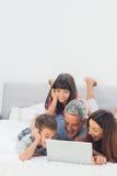 Glückliche Familie, die auf Bett unter Verwendung ihres Laptops liegt Stockfotos
