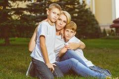 Glückliche Familie, die auf dem Gras im Sommer sitzt Stockfotografie