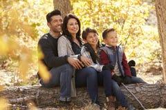 Glückliche Familie, die auf gefallenem Baum in einem Wald weg schaut sitzt Stockfotografie