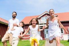 Glückliche Familie, die auf Wiese vor Haus läuft Stockbilder