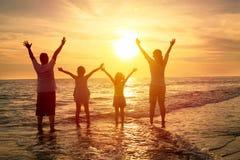 Glückliche Familie, die den Sonnenuntergang auf dem Strand aufpasst Stockfoto