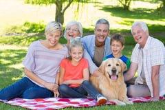 Glückliche Familie, die an der Kamera mit ihrem Hund lächelt Stockfotos