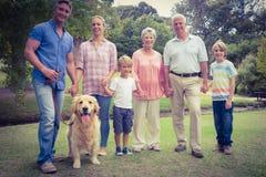 Glückliche Familie, die an der Kamera mit ihrem Hund lächelt Lizenzfreies Stockbild