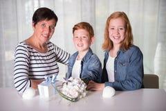 Glückliche Familie, die Geburtstag mit Geschenken und Blumen feiert Stockfotos