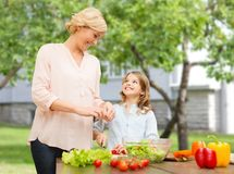 Glückliche Familie, die Gemüsesalat für Abendessen kocht Stockfoto