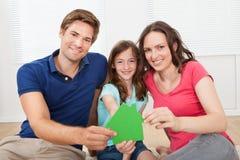Glückliche Familie, die grünes Haus-Modell At Home hält Stockfoto