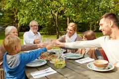Glückliche Familie, die im Sommergarten zu Abend isst Lizenzfreies Stockfoto