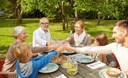 Glückliche Familie, die im Sommergarten zu Abend isst Stockfotografie