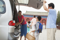 Glückliche Familie, die Material heraus vom Auto, bereitend für Picknick nimmt vor Lizenzfreie Stockfotografie