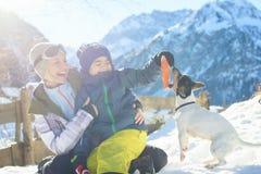 Glückliche Familie, die mit einem Hund in einer Sonne in den österreichischen Alpen spielt Stockfotografie