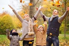 Glückliche Familie, die mit Herbstlaub im Park spielt Stockbild