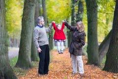 Glückliche Familie, die mit Kleinkindmädchen im Herbstpark spielt Stockbilder