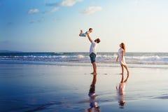 Glückliche Familie, die mit Spaß auf Sonnenuntergangseestrand geht Stockbilder