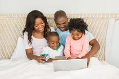 Glückliche Familie, die online mit Laptop kauft Stockbild