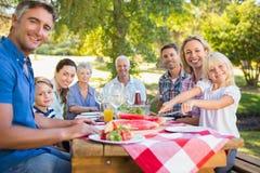 Glückliche Familie, die Picknick hat und amerikanische Flagge hält Lizenzfreies Stockfoto