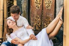 Glückliche Familie, die romantischen Flitterwochenfeiertag auf schwarzem Sandstrand genießt Stockfotografie