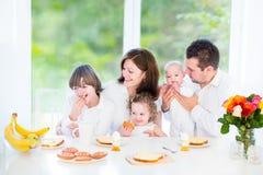 Glückliche Familie, die am Sonntag Morgen frühstückt Stockfoto